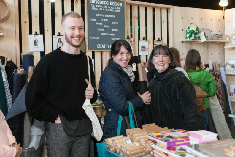 Young man and two women browse products in a vendor booth.