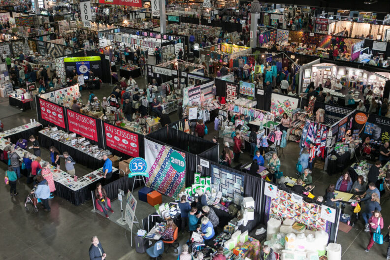 Shoppers walk between a number of vendor booths at Expo.