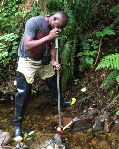 Lambert Ngenzi standing in mountain stream with water sampling tools taking water velocity measurements