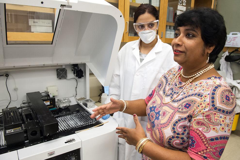 Susmita Bose talking to lab assistance next to a machine