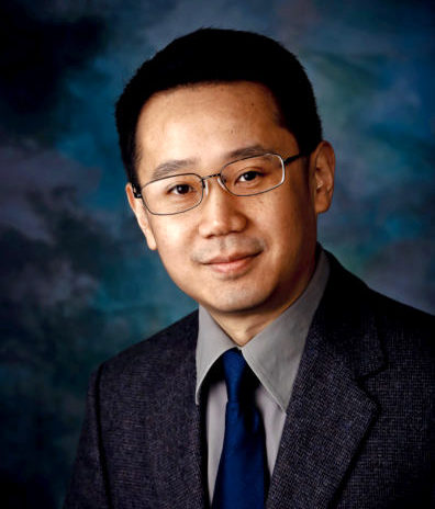 Ming Xian, profile photo in suit and tie against abstract background.