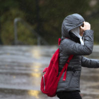 Female student in coat with hood up running in the rain.