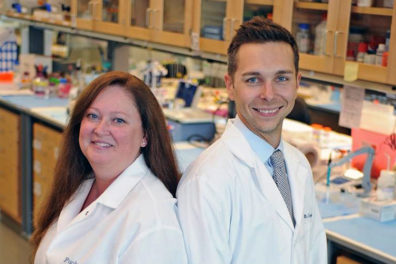 Rita Fuchs, left, and Ryan McLaughlin in a lab posing in profile