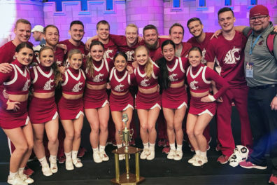 WSU cheer squad standing behind their trophy as they pose for a picture.