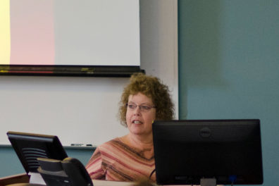 Professor Naomi Lungstrom at her desk speaking to a classroom.