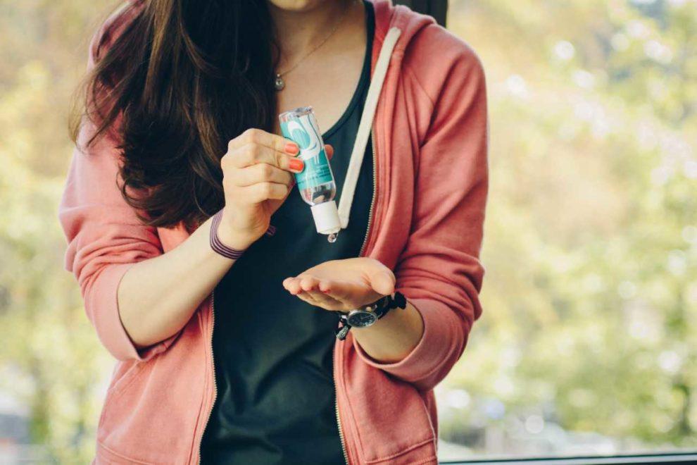 Student using hand sanitizer to help avoid illness