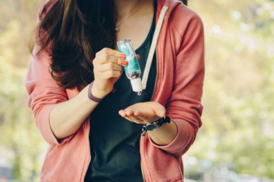 Student squeezing hand sanitizer from a bottle into her hand