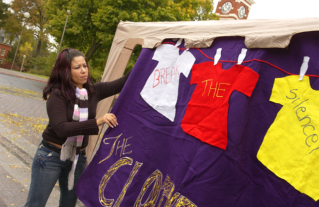 "Image of a student hanging a sign that says ""Break the Silence!"" at a Clothesline Project demonstration."