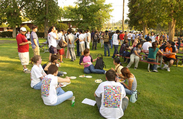Image of students sitting in a circle at the International Student Picnic at Reaney Park