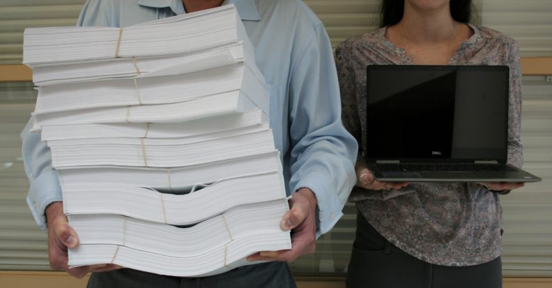 A close-up shot of a man and woman standing in front of a wall. We can only see their midsections. The man is holding a stack of papers so heavy they are bowing under their own weight. The woman holds a lightweight laptop computer at chest height.