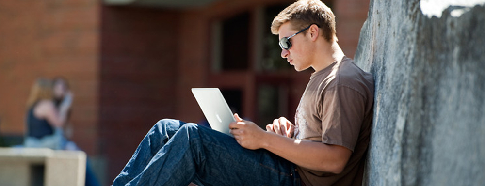 student leans against rock, uses laptop