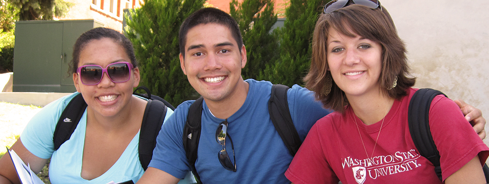 three smiling students sit in a row in the sunshine