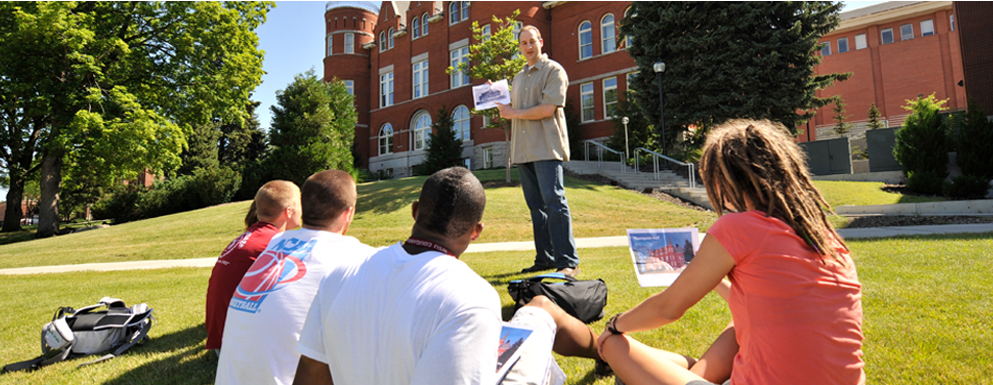 Instructor gestures to printed sheet as students look on, seated on sunny lawn