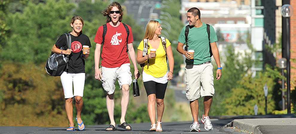 Photo: four smiling students in summer clothes walk through campus.
