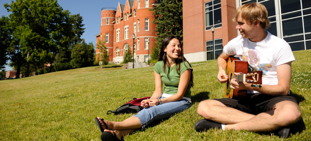 Photo: Students sit on grass on Thompson Flats, playing guitar.