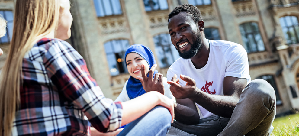 Photo: Diverse group of students interact smiling while seated outdoors.