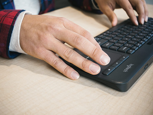 student hands typing on a computer keyboard