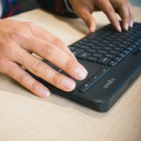 student hands typing on keyboard