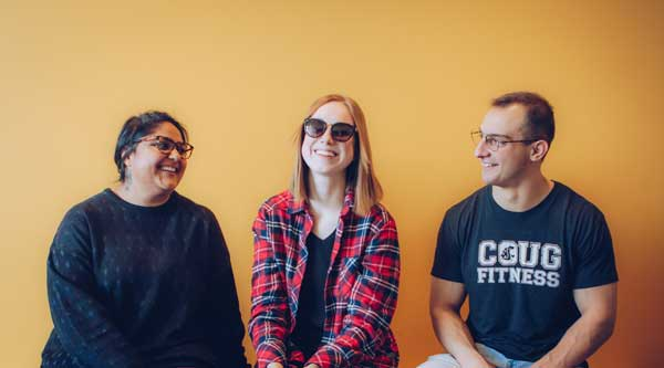Three students against a yellow wall wearing TOMS brand eyewear