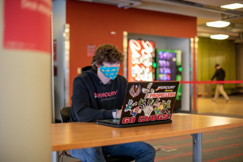 Male student sitting at a table working on an open laptop in the Compton Union Building.