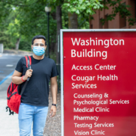 Student wearing mask standing in front of Washington Building.