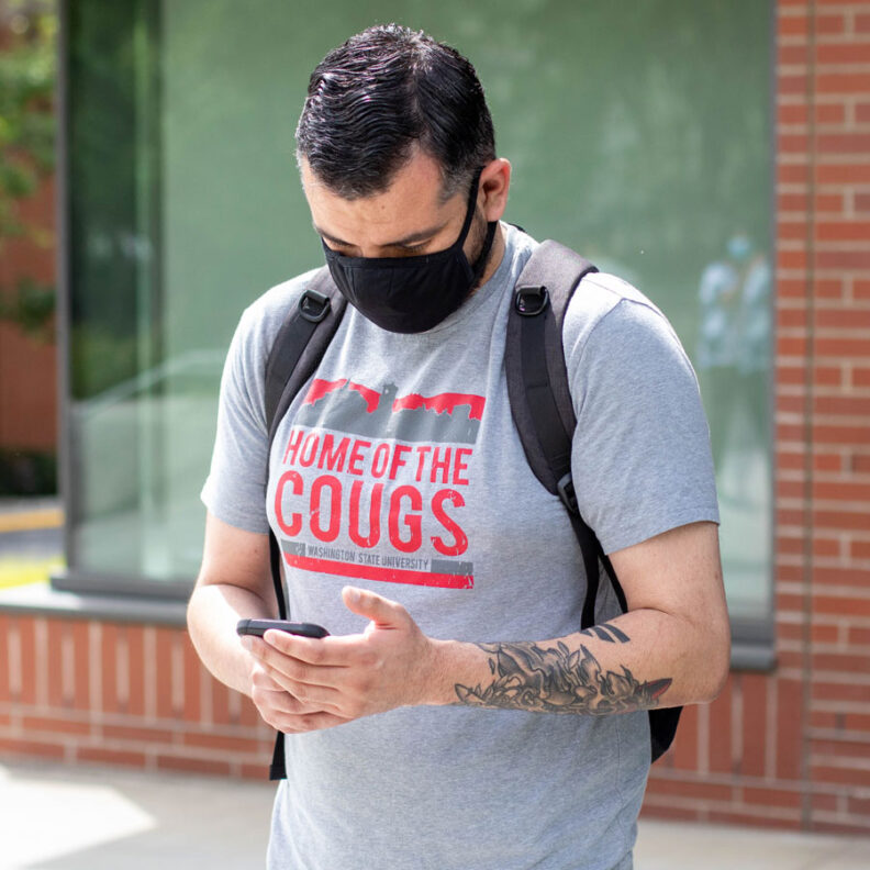 Student with mask looking at cell phone outside