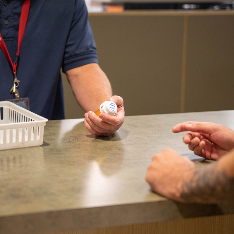 WSU Pharmacy worker serving student at counter with medication.