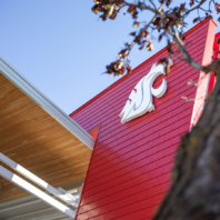 Exterior closeup of the WSU spirit mark in white against the red backdrop on the Chinook Student Building