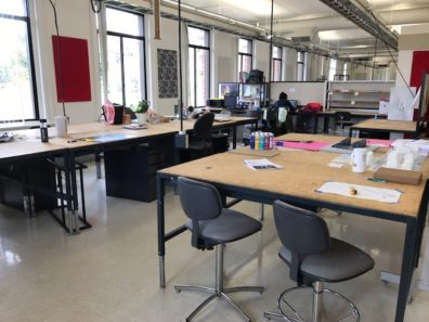 Pictured is the design studio in Carpenter Hall containing individual work spaces, such as high-adjustable tables, chairs, and pin-up boards, along with extension cords on each space.