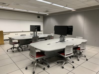 The pictured room contains several meeting tables, chairs and monitors at the center of the table.