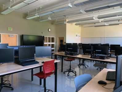 The room contains several dual-monitor computer stations on height-adjustable work tables and stool chairs as well as a SMART board in the front center of the room.