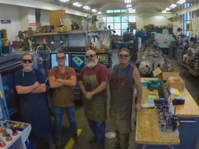 The image shows four men standing in a row wearing safety goggles and aprons surrounded by shop equipment.