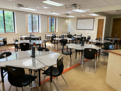 The image shows meeting tables and chairs with a projector at the end of the Bio-engineering Instruction Room in Wegner 205.