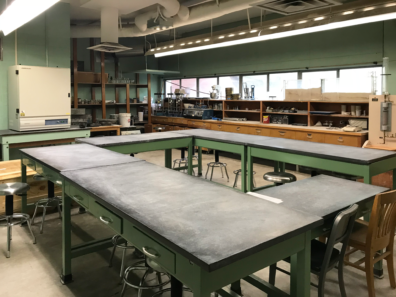 The picture shows tables and chairs in the middle of the room as well as soils equipment in the surrounding area to use for research.