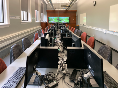 The room contains several computer stations as well as presentation monitors on each end.