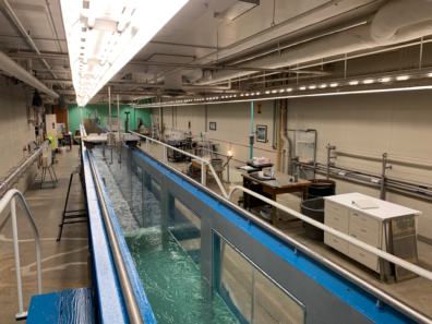 The image features a Dam simulator as well as other hydraulic equipment being used in the Sloan Hydraulics Lab.