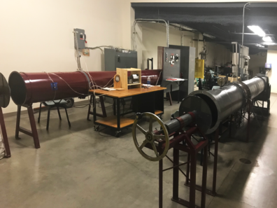 The image shows a centrifugal fan, an axial fan wind tunnel, and several other mechanical equipment utilized in the Experimental Design Lab.