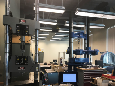 The image shows two tensile testing machines as well as other material and mechanical equipment being used in the lab.