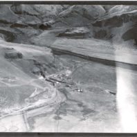 An aerial view showing the rockshelter from the east, the trenches on the floodplain, the camp, and the Palouse River in the background, 1968