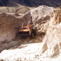 Archaeologist Bennie Keel shown operating a backhoe to deepen one of the trenches dug on the floodplain outside the Marmes Rockshelter, July 1968.