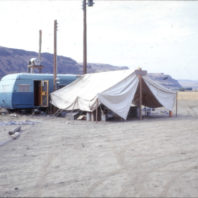 The lab for processing artifacts consisted of a two-tone blue housetrailer and a large white canvas tent located on the floodplain, July 1968