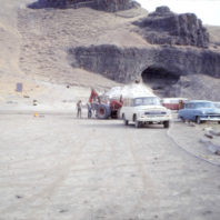 This view of the rockshelter from the floodplain shows the vehicles parked in the camp area, July 1968