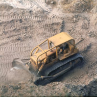 A view from the ground surface down into one of the trenches, showing the bullddozer at work, July 1968