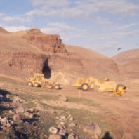 This view shows heavy equipment leveling the surface of the floodplain in preparation for the building of the coffer dam to protect the site, November 1968