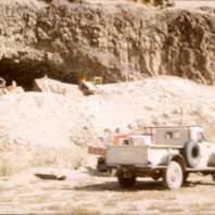 A view of the Marmes Rockshelter from the floodplain July 1962 showing the screen and piles of screened soil and the project vehicles