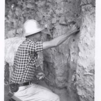 Roald Fryxell, kneelinig in an excavation unit, is tagging geologic strata using paper tags on metal pins, 1962