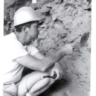 Richard Daugherty, pipe in hand, examines the sidewall of an excavation unit inside the Marmes Rockshelter, 1962