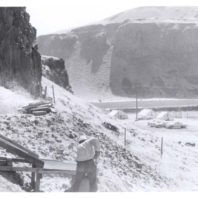 A view across the floodplain and the Palouse River showing an excavator shoveling dirt sent down from the rockshelter into a screen. In the background you can see the camp tents.