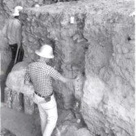 Roald Fryxell, standing inside an excavation unit, is examining a layer of volcanic ash, 1962