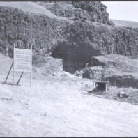 The exterior of the Marmes Rockshelter viewed from the floodplain showing the early excavations and the sign put up to inform the many public visitors
